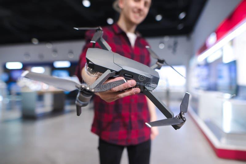 有一quadcopter的正面年轻人在他的手上在寄生虫商店 在电子商店买dron 库存照片