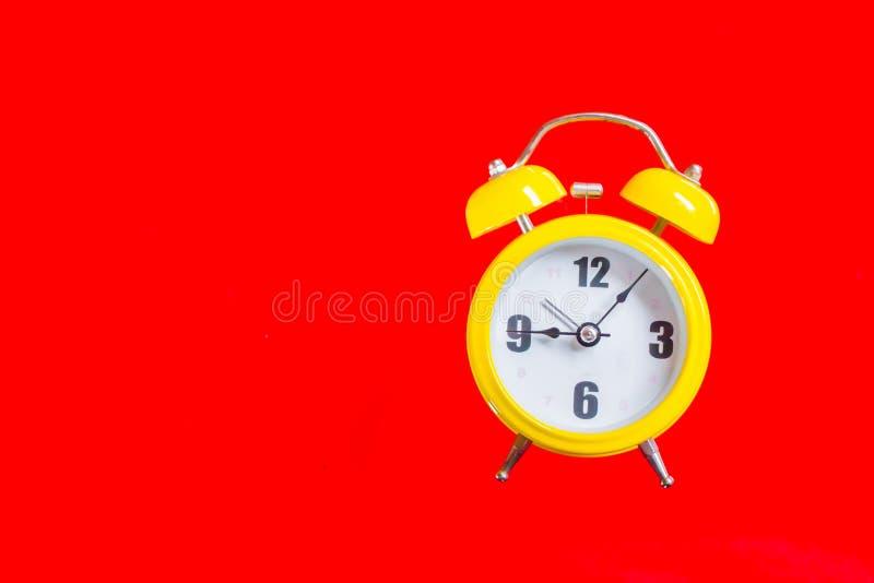 有九五分钟老牌的,在红色背景的顶视图减速火箭的黄色闹钟 免版税库存照片
