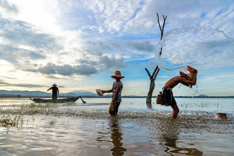 有亚洲男孩和女孩行动的渔夫,当鱼网使用室外在河和湖早晨日出的 图库摄影