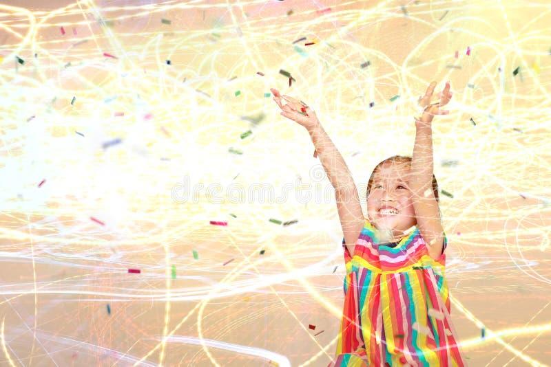 有五颜六色的五彩纸屑和轻的背景的两次曝光愉快的小孩女孩 新年快乐或祝贺概念 库存图片