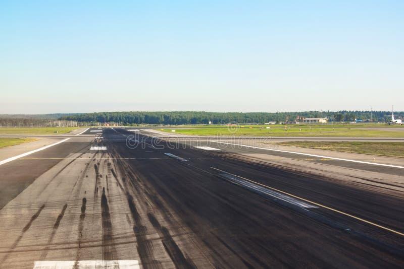 有任意飞机的橡胶轮子踪影的跑道为起飞和着陆在机场 免版税库存照片