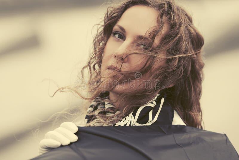 有伞的哀伤的美丽的时尚妇女在城市街道上 免版税库存图片