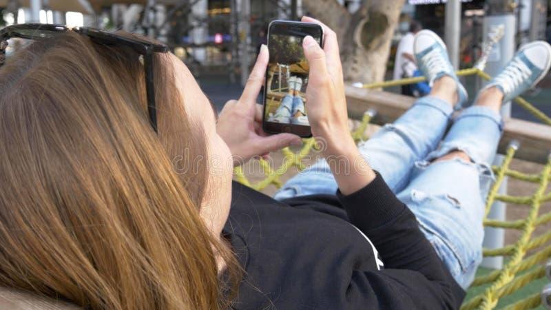 有休息在城市吊床,妇女腿作为selfie  库存图片