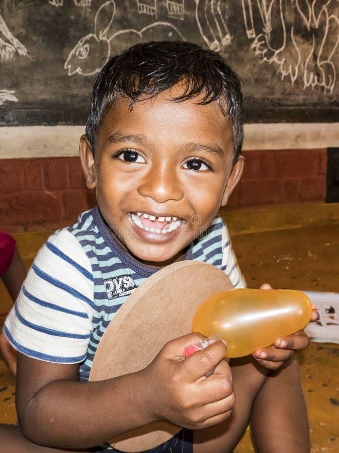 有使用与气球的大微笑表示的印度小男孩 免版税库存照片