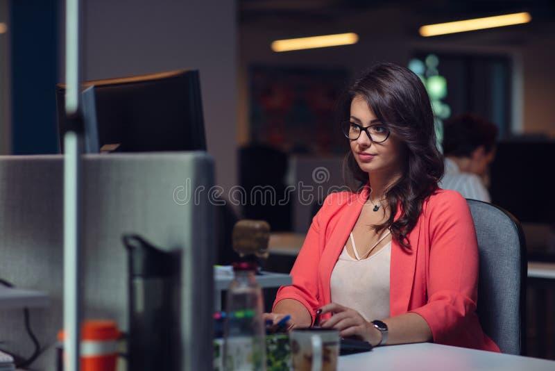 有便携式计算机的美丽的企业夫人在办公室 库存图片