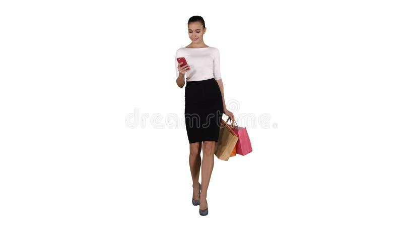 有做图片的智能手机的愉快的年轻女人她的购物带来在白色背景 免版税库存图片
