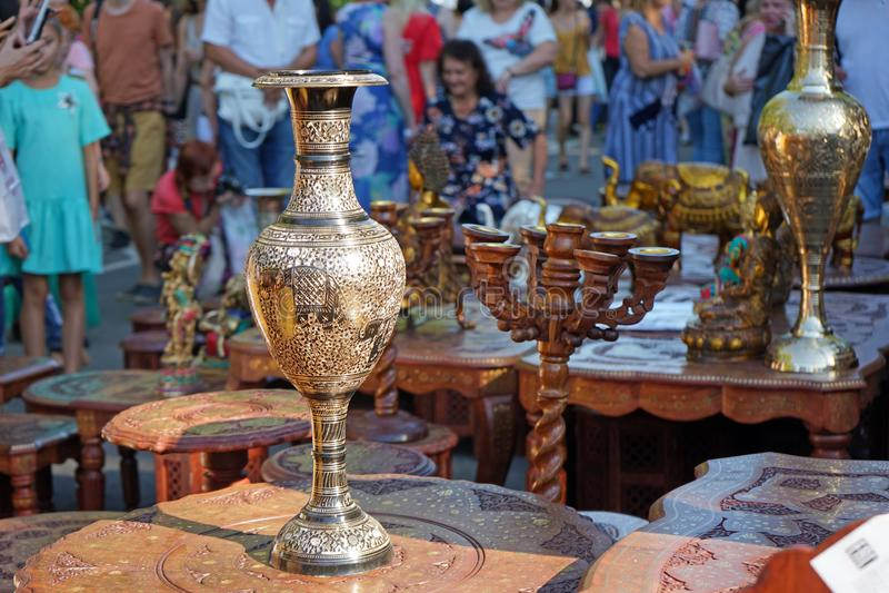 有印度装饰品的被镀金的花瓶在桌上由桃花心木制成 免版税库存照片