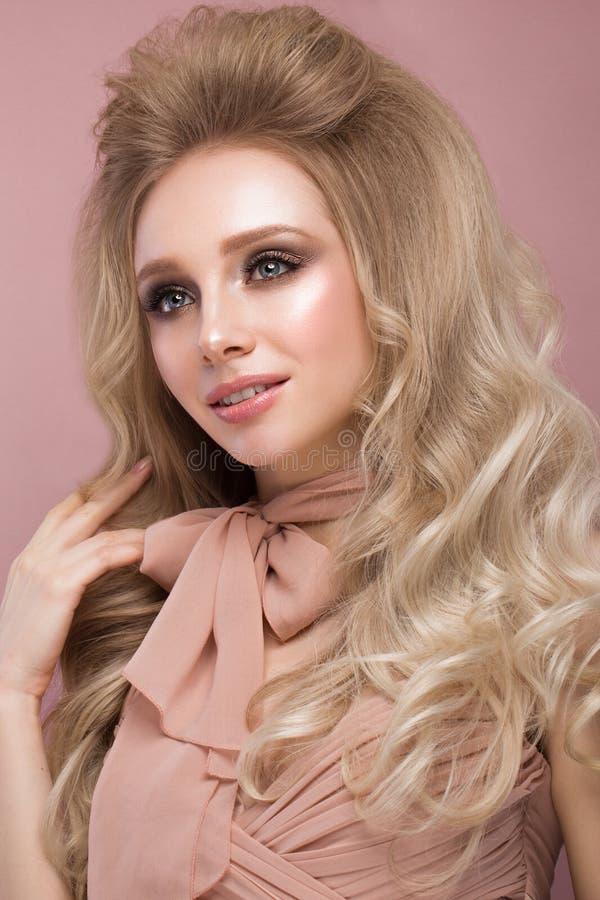 有卷毛头发的美丽的白肤金发的女孩,在桃红色衣裳看起来一个玩偶,有迷人的组成 秀丽表面 免版税库存图片