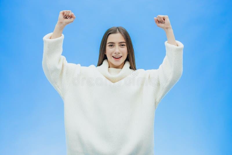 有吸引力的女孩年轻人 使用庆祝胜利的黑色头发 挥动与他的拳头和精采微笑 在蓝色 免版税库存图片