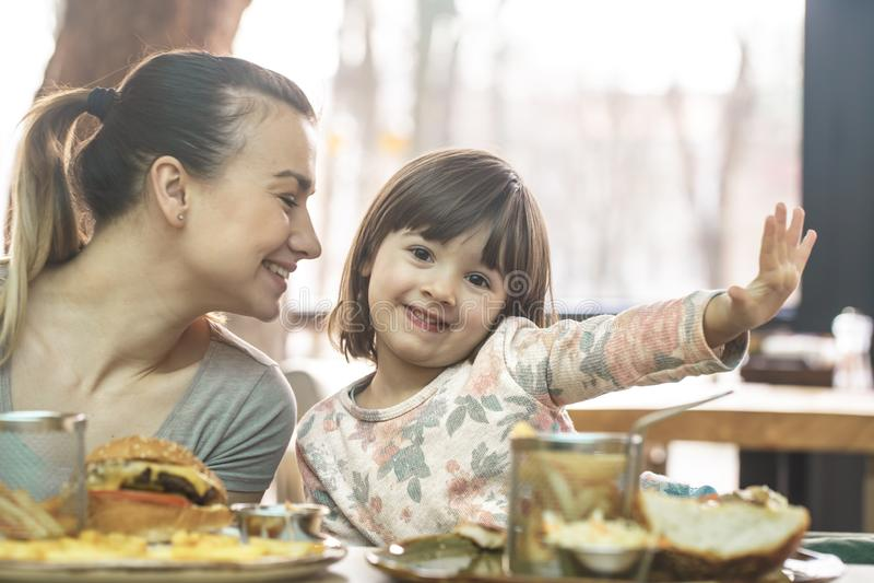 有吃在咖啡馆的一个逗人喜爱的女儿的妈妈便当 免版税图库摄影