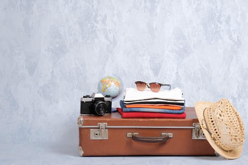 有夏天辅助部件的古板的旅行手提箱:玻璃,盒衣物,减速火箭的照片照相机,秸杆在灰色后面的海滩帽子 库存图片