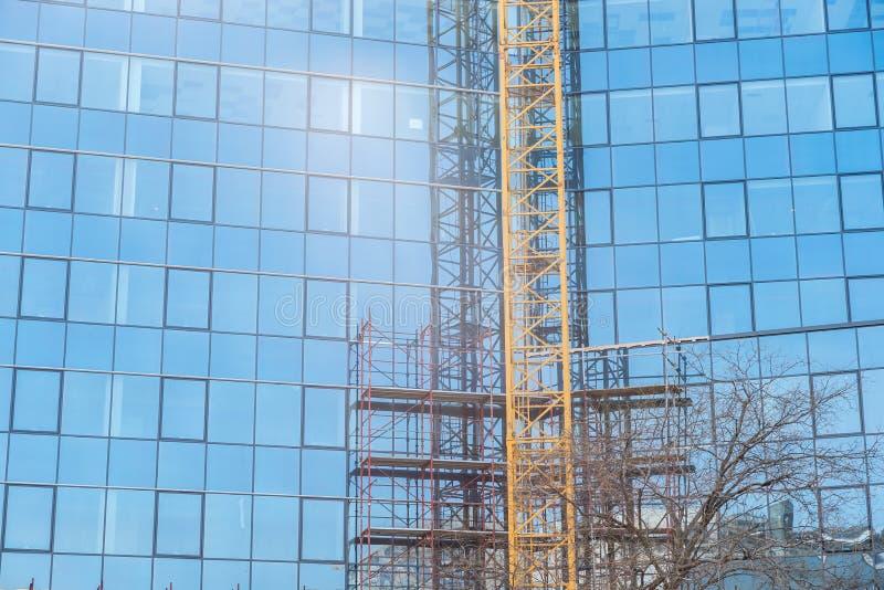 有大玻璃窗门面绞刑台和起重机零件的新的现代建筑学企业大厦工地工作 库存照片