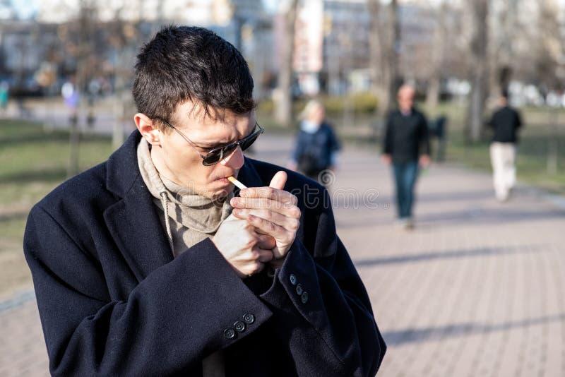 有太阳镜的年轻偶然吸烟者人在黑色大衣抽烟的香烟外面在公园 库存图片