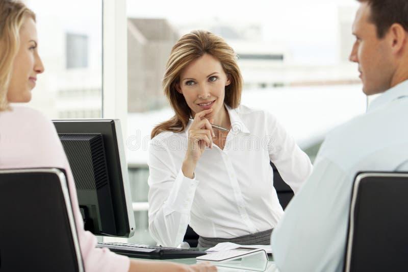 有夫妇的财政顾问在会议上在办公室-律师提供忠告的供以人员和妇女-与客户的不动产房地产经纪商 库存图片