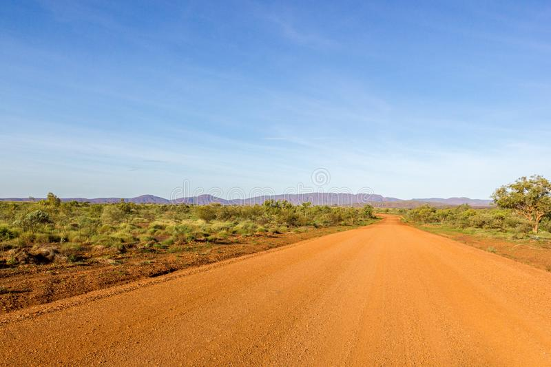 有多云天空蔚蓝的红色澳大利亚农村路,澳大利亚西部 免版税库存图片