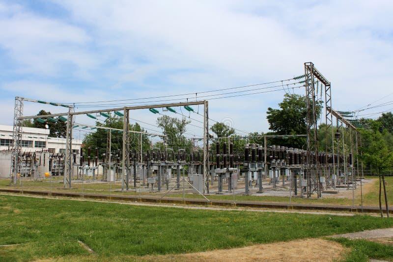 有多台电能变压器的工业能源厂和玻璃和陶瓷绝缘体有关到密集的导线 免版税图库摄影