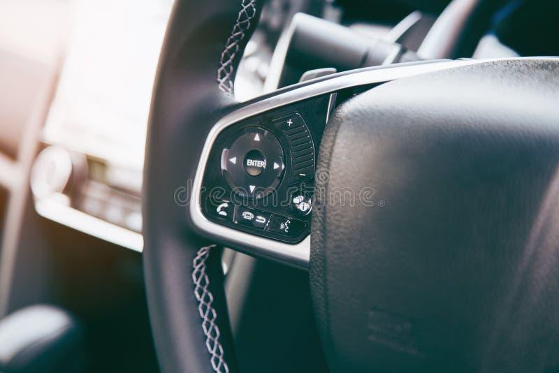 有多功能按钮的快的控制的,在汽车的特写镜头现代黑方向盘 库存图片