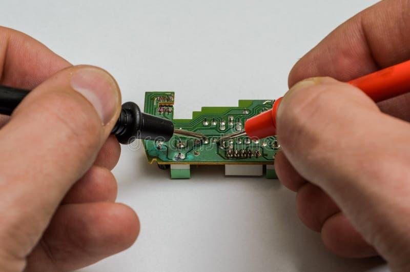 有多用电表的主要工程师测试和修理微集成电路 库存照片