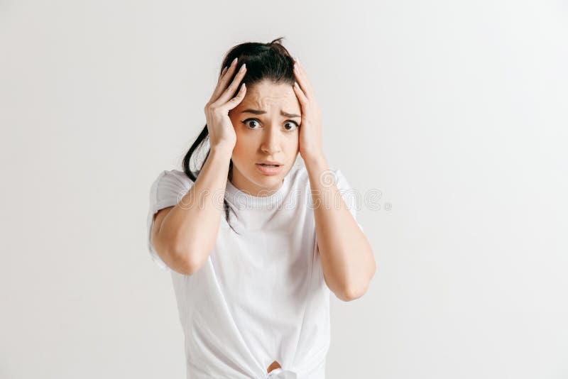 有头疼妇女 查出在灰色背景 库存图片