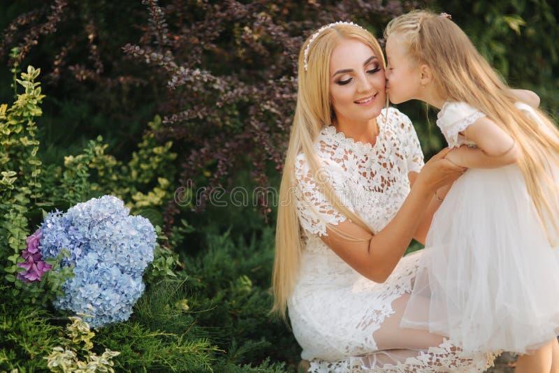 有女儿的妈妈白色礼服的在公园花费时间 金发女性 母亲编织猪尾女儿外部 图库摄影