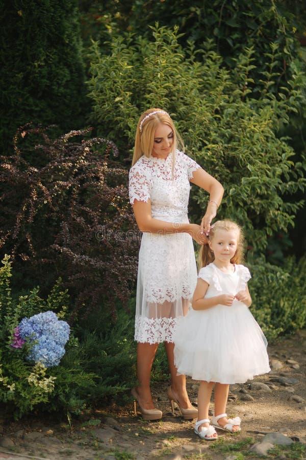 有女儿的妈妈白色礼服的在公园花费时间 金发女性 母亲编织猪尾女儿外部 免版税库存图片