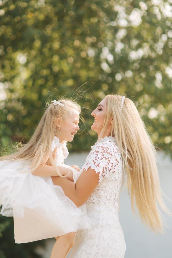 有女儿的妈妈白色礼服的在公园花费时间 金发女性 母亲编织猪尾女儿外部 免版税图库摄影