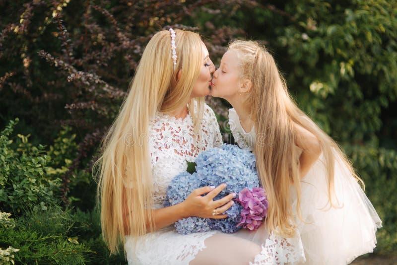 有女儿的妈妈白色礼服的在公园花费时间 金发女性 母亲编织猪尾女儿外部 免版税库存照片