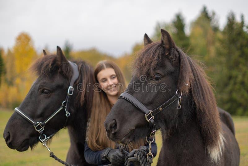 有她的两匹冰岛马的微笑的年轻瑞典妇女 免版税图库摄影