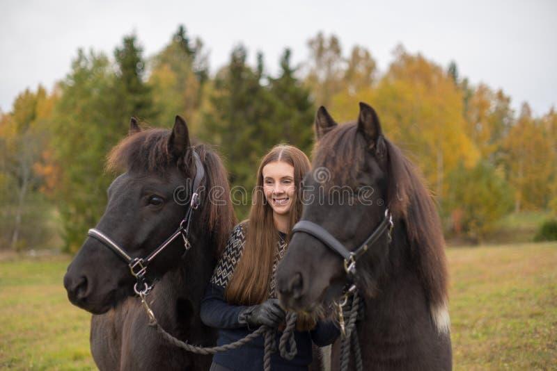 有她的两匹黑冰岛马的微笑的年轻瑞典妇女 库存照片