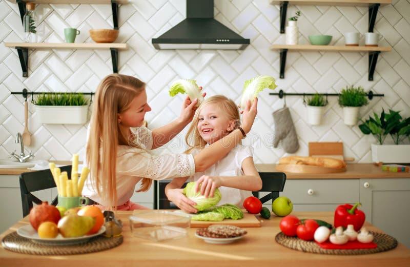 有她的女儿的母亲在准备与新鲜蔬菜的厨房里健康食品 免版税库存图片