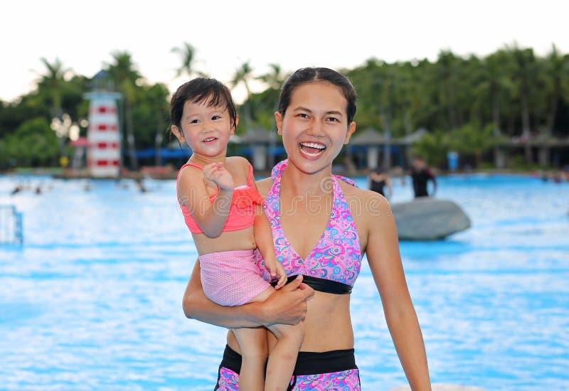 有她的母亲的俏丽的女孩户外游泳场的 免版税库存图片