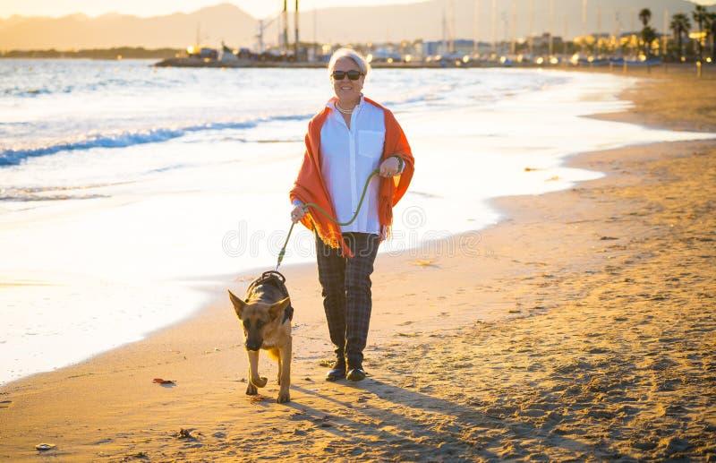 有她的走在海滩的德国shepard狗的愉快的可爱的资深妇女在秋天日落 免版税库存图片