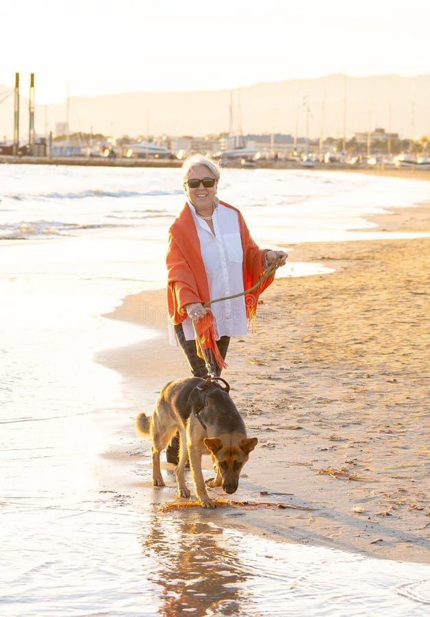 有她的走在海滩的德国shepard狗的愉快的可爱的资深妇女在秋天日落 免版税库存照片