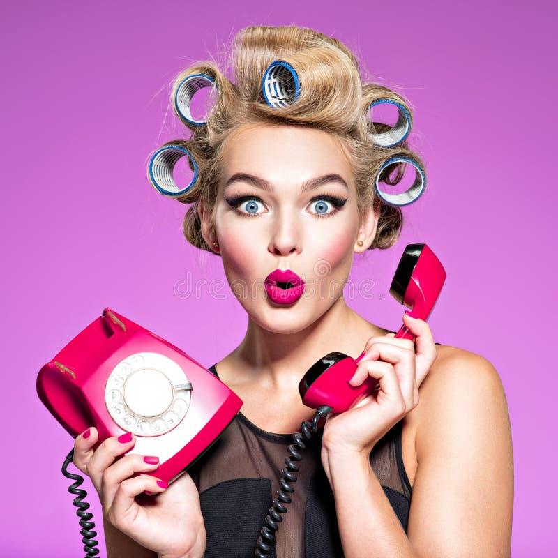 有奇迹面孔的年轻女人拿着减速火箭的电话 库存图片