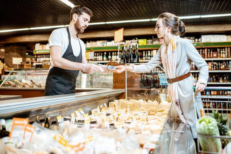 有妇女客户的乳酪卖主在超级市场 免版税库存图片