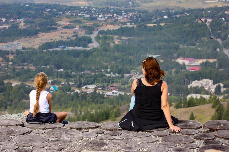 有孩子的一名妇女坐在峭壁和休息边缘 库存图片