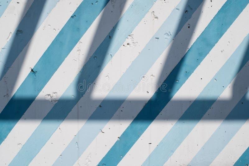 有对角蓝色和蓝色条纹和阴影的被绘的混凝土墙 免版税库存图片