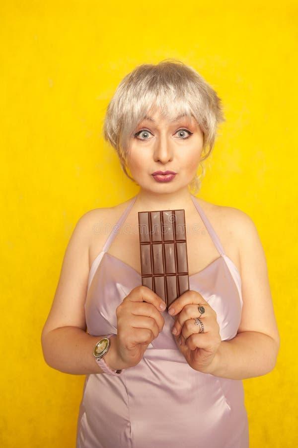 有巧克力块的俏丽的胖的女孩在黄色演播室坚实背景 库存照片