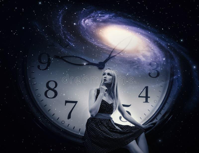 有巨型时钟和星系的妇女 免版税库存照片