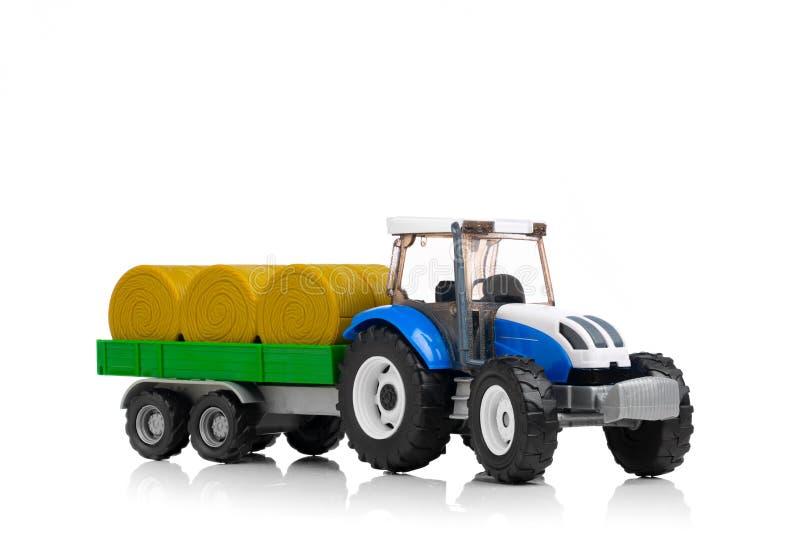 有干草拖车的农用拖拉机玩具,隔绝在白色 库存图片