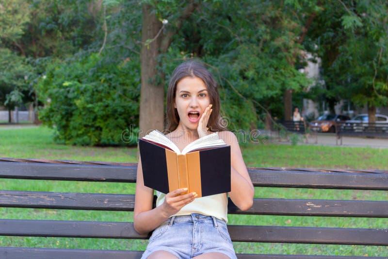 有广泛开放肯定和嘴的惊奇的年轻女人和在面颊的一只手读一本书户外 免版税库存图片
