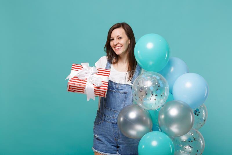 有庆祝与五颜六色的气球的礼物丝带的微笑的年轻女人举行红色镶边当前箱子被隔绝  库存照片