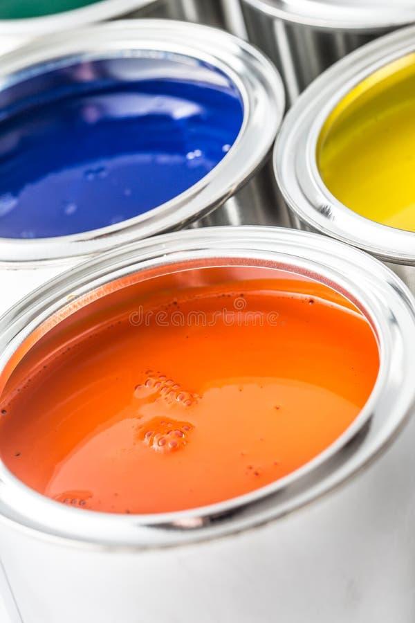 有很多在白色桌上的多彩多姿的油漆罐头 免版税库存照片