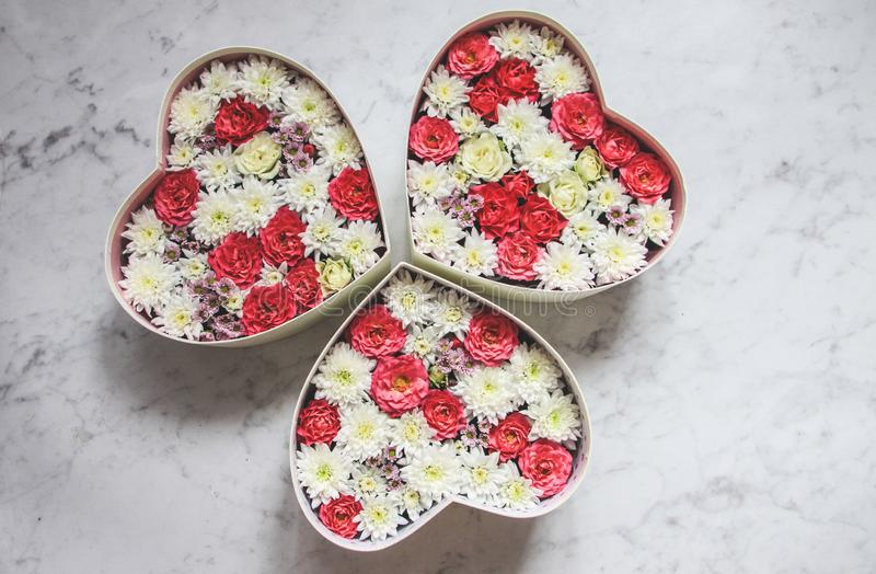 有心形的花的礼物盒在灰色大理石背景 库存照片