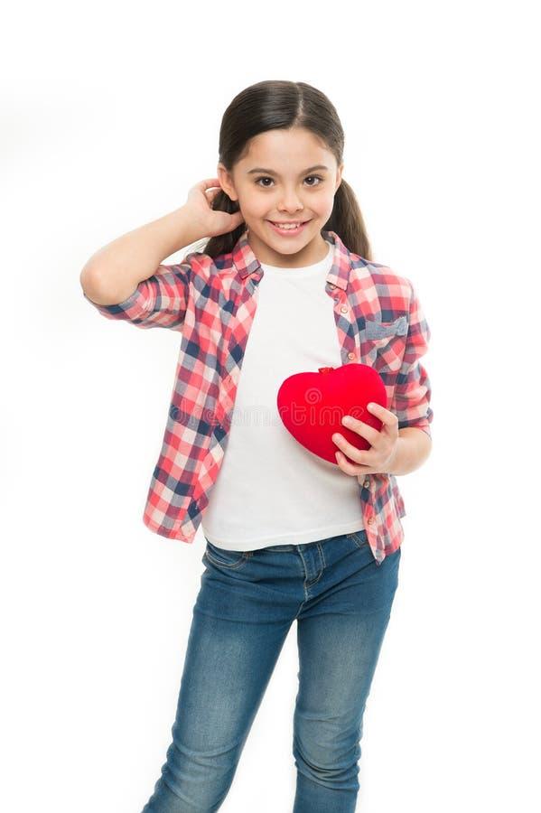 有心脏问题和心伤 拿着红色心脏的小女孩 表现出的小孩爱在情人节 逗人喜爱 免版税库存照片