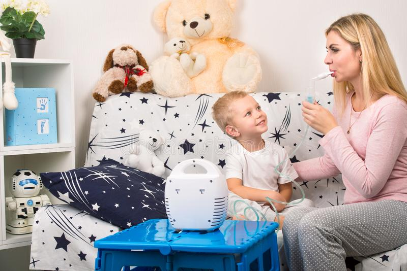 有在家做与雾化器的儿子的少妇吸入 做吸入的一个幼儿的母亲 免版税库存图片