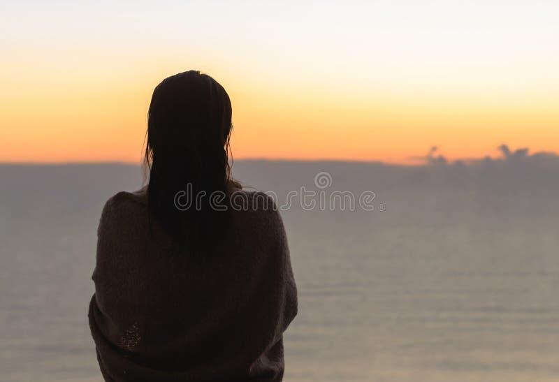 有在有站立玻璃阳台清早的咖啡的一条毯子包裹的湿头发的赤裸美丽的女性在sunris 免版税库存图片