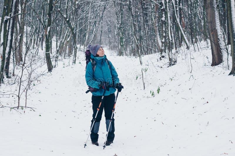 有在旁边远足通过冬天森林的背包和迁徙的杆神色的少女 库存照片