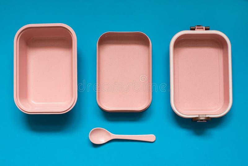 有匙子的空的桃红色bento饭盒在蓝色背景 库存照片