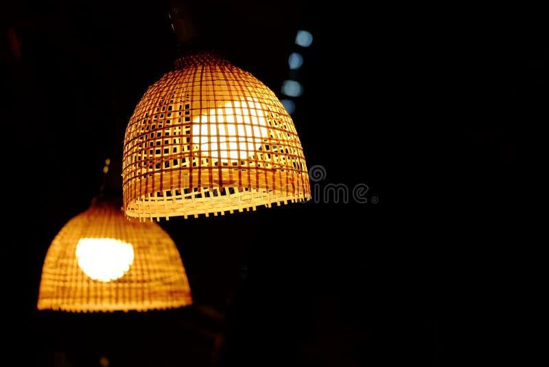 有垂悬从一块室天花板的电灯泡的竹灯笼有黑暗的背景 免版税库存照片